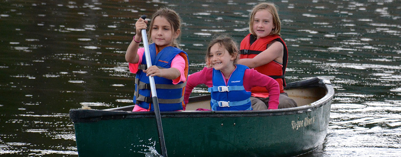 Canoeing on the lake at camp with smiles
